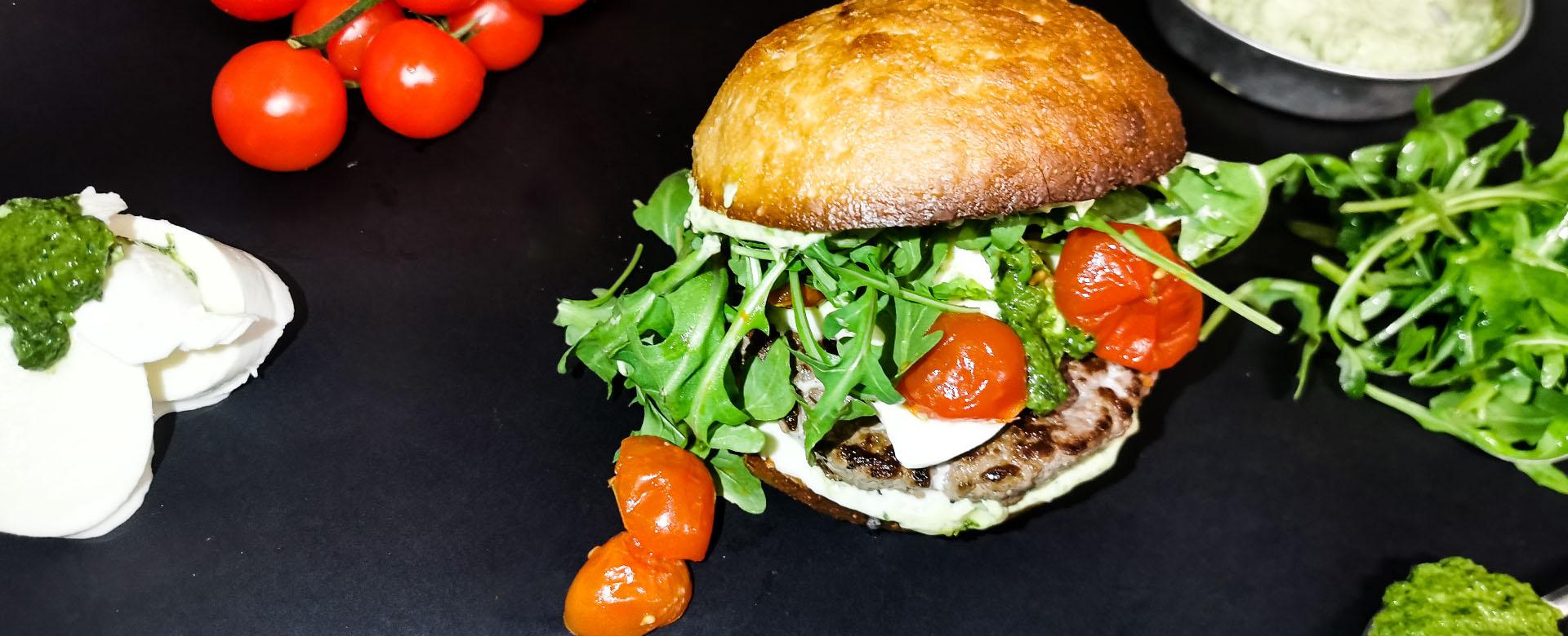 Vista dall'alto di ITALO: un hamburger senza glutine con rucola, mozzarella e pomodori confit da ordinare a domicilio