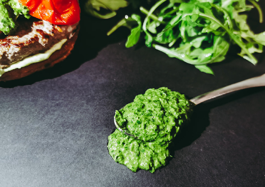 Salsa artigianale al basilico fresco su cucchiaio, sullo sfondo c'è ITALO un hamburger