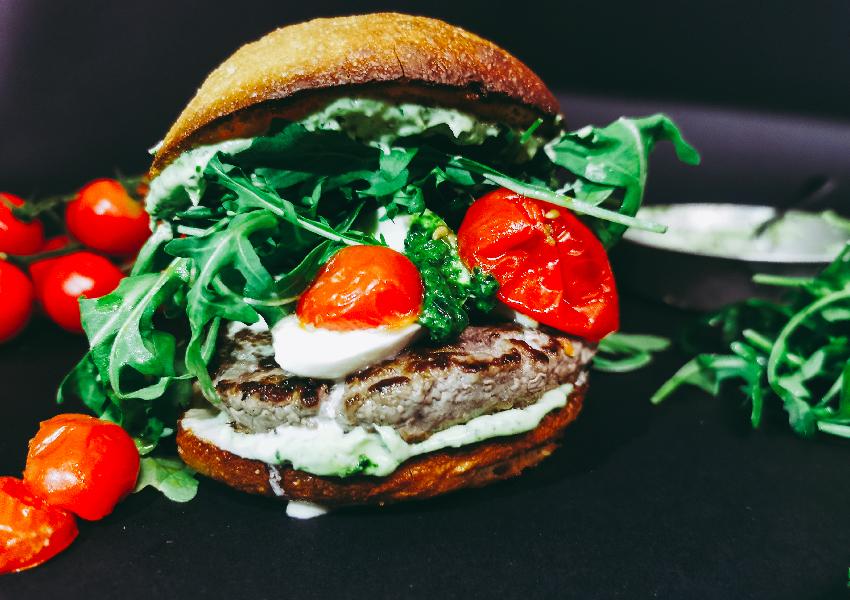 Foto frontale in primissimo piano di ITALO: un hamburger senza glutine con rucola, mozzarella e pomodori confit da ordinare a domicilio