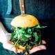 Una donna con una grembiule di jeans e pelle nera tiene sul palmo della mano un hamburger; si tratta di YODA, uno degli hamburger senza glutine di Erudito, che mostra tutti i suoi ingredienti: cicoria, hamburger, rucola, provola, 'nduja