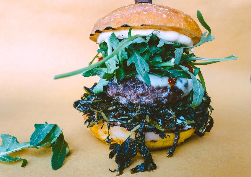 YODA: Hamburger artigianale in primo piano con sfondo neutro e rucola come decorazione per set fotografico