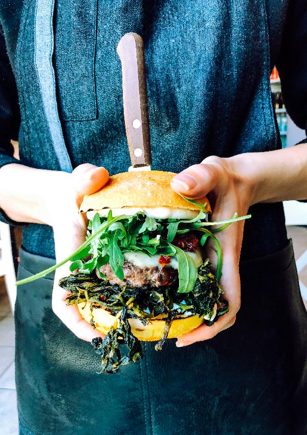 Una donna con una grembiule di jeans e pelle nera, tiene tra entrambe le mani un hamburger. Si tratta di YODA, uno degli hamburger senza glutine di Erudito, che mostra tutti i suoi ingredienti: cicoria, hamburger, rucola, provola, 'nduja